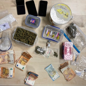 Drogen und Bargeld auf einem Tisch ausgebreitet.