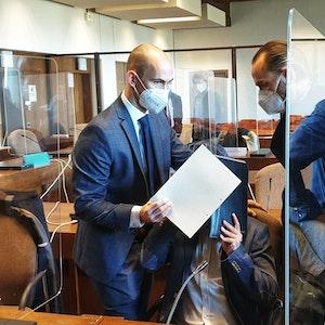 Prozessauftakt: Der Angeklagte hält sich Akten vor das Gesicht. Die Rechtsanwälte verdecken den Angeklagten mit Dokumenten.