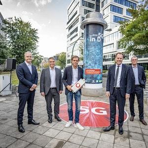Alle Beteiligten stehen vor einer Litfaßsäule in Düsseldorf.