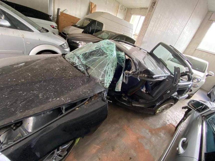 Ein demoliertes Auto steht in einer Garage.
