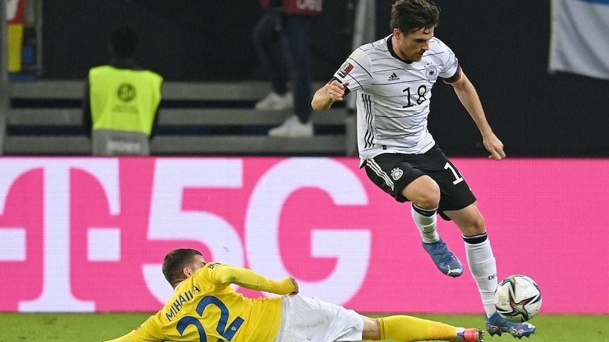 DFB-Nationalspieler Jonas Hofmann (r.), bei Fußball-Bundesligist Borussia Mönchengladbach unter Vertrag, behauptet im Duell mit Valentin Mihaila (l.) den Ball während des Länderspiels gegen Rumänien am 8. Oktober 2021 in Hamburg. Hofmann springt über das Bein des Gegenspielers.
