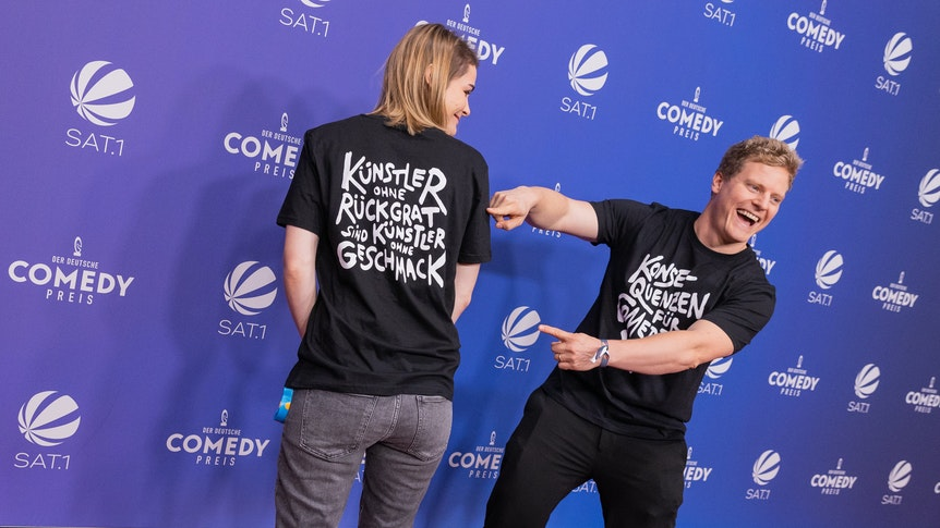"""Wegen Luke Mockridge: Hazel Brugger und ihr Mann Thomas Spitzer mit T-Shirt mit der Aufschrift """"Konsequenzen für Comedian XY"""" kommen über den Roten Teppich zur Verleihung des Deutschen Comedypreises 2021."""