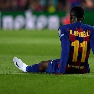 Ousmane Dembélé sitzt bei einem Spiel des FC Barcelona nach einer Verletzung auf dem Rasen des Camp Nou.