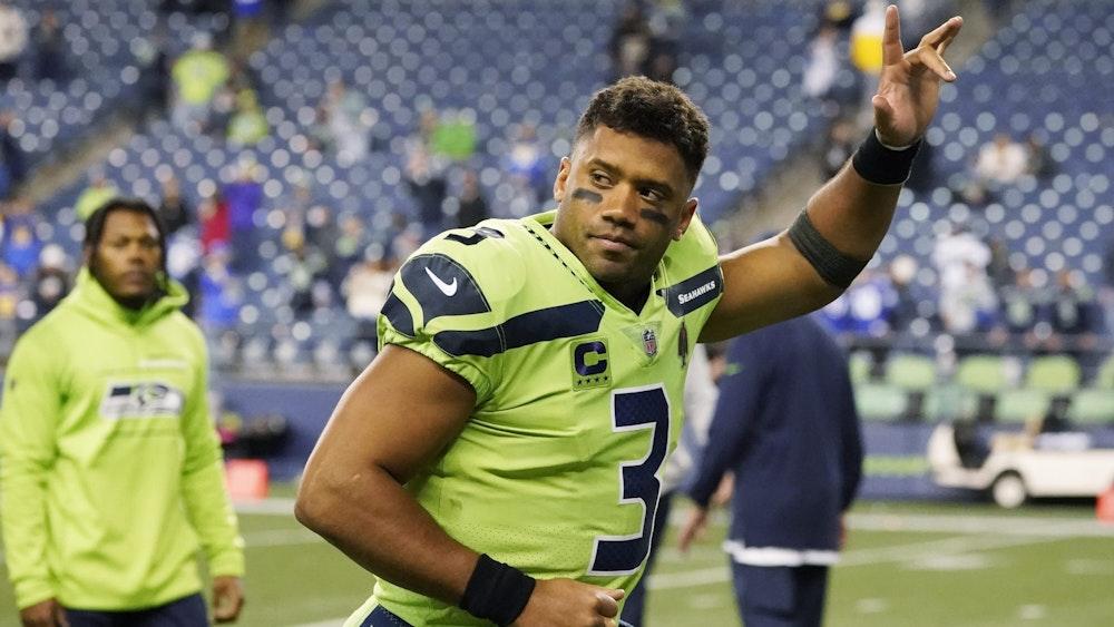 Russell Wilson hält beim Spiel der Seattle Seahawks den linken Arm nach oben.