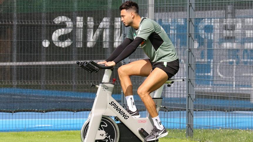 Ramy Bensebaini von Borussia Mönchengladbach sitzt am 18. Juli 2021 auf einem Spinning-Rad während des Trainingslagers in Harsewinkel. Bensebaini schaut nach vorne und radelt.