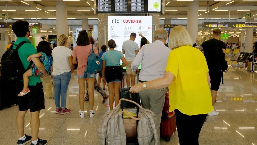 Menschen informieren sich am 1. August 2021 im Abflugbereich des Flughafens von Palma de Mallorca über Corona-Regeln. Für die Herbstferien wurden zwei getrennte Schlangen für geimpfte und ungeimpfte Reisende eingerichtet.