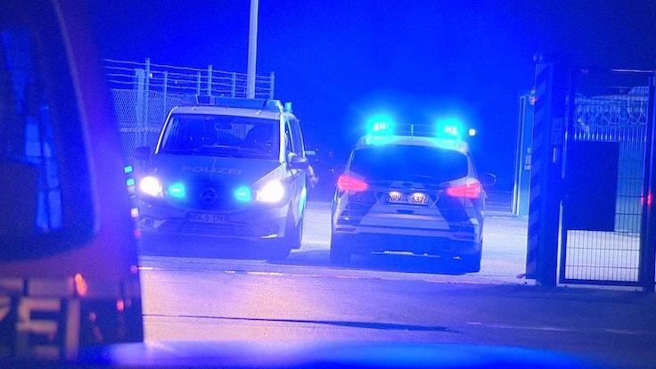 Polizisten passieren in Polizeifahrzeugen ein Tor am Flughafen Weeze, wo ein Auto einen Zaun an einer Rollbahn durchbrochen hat.