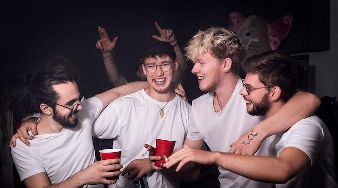 Band King Loui feiert Arm in Arm, mit Bechern und Zigaretten in den Händen.