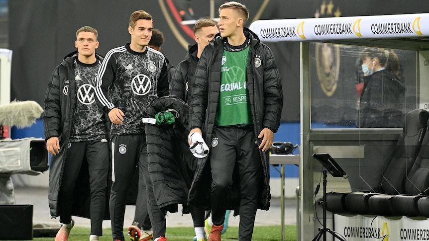 Die Nationalspieler Florian, Florian Neuhaus und Nico Schlotterbeck (v.l.n.r.) schreiten am 8. Oktober 2021 in Hamburg zur Reservebank der DFB-Elf. Neuhaus hält seinen Mantel in der Hand.