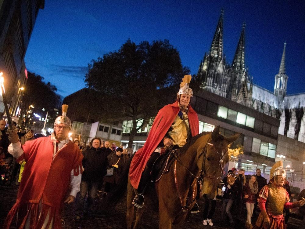 Ein Darsteller des Heiligen Martin reitet 2017 bei einem Zug am Kölner Dom vorbei.