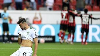 Ramy Bensebaini, hier am 21. August 2021, kniet enttäuscht auf dem Rasen, im Spiel von Borussia Mönchengladbach gegen Bayer Leverkusen.