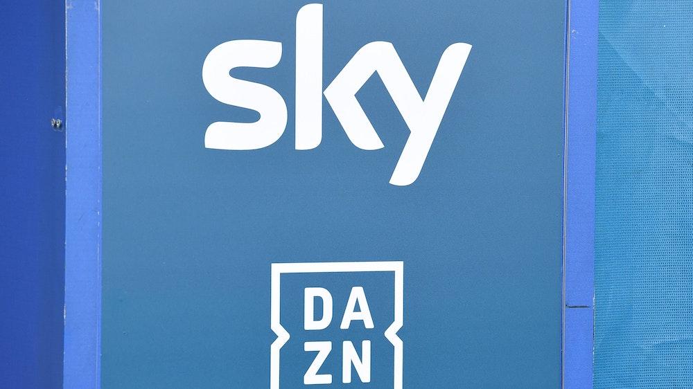 Die Logos der TV-Anbieter Sky und DAZN sind auf eine Tafel gedruckt.
