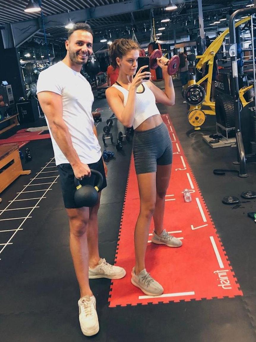 Personal Trainer Oguz Kaan mit Vanessa Fuchs im Fitnessstudio.