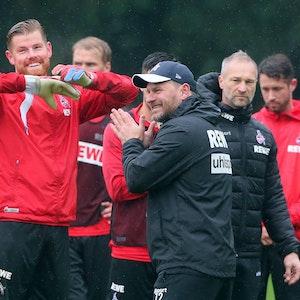 Torwart Timo Horn und Trainer Steffen Baumgart lachen während des Trainings gemeinsam.