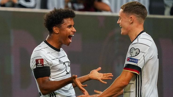 Florian Wirtz geht auf Karim Adeyemi zu. Adeyemi lacht.