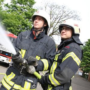 Zwei Feuerwehrmänner halten einen Löschschlauch.