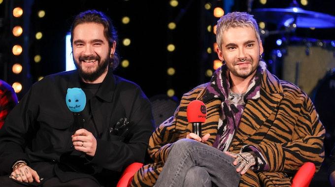 Tom und Bill Kaulitz von der Band Tokio Hotel sitzen während einer Radioshow auf einer Bühne mit jeweils einem Mikrofon in der Hand.