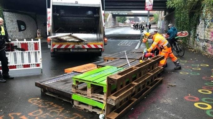 Mitarbeiter der Kölner AWB entfernen Aufbauten am Eifelwall.
