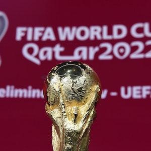 WM-Pokal vor einem Banner der WM 2022 in Katar bei der UEFA-Vorrundenauslosung