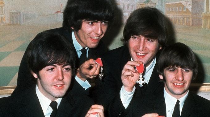"""Die britische Popgruppe """"The Beatles"""" (v.l.) Paul McCartney, George Harrison, John Lennon und Ringo Starr mit den Orden """"Member of the Order of the British Empire"""" auf einem Foto vom 26. Oktober 1965."""