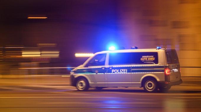 Ein Polizeiwagen mit Blaulicht fährt am Silvesterabend durch die Innenstadt zu einem Einsatz.