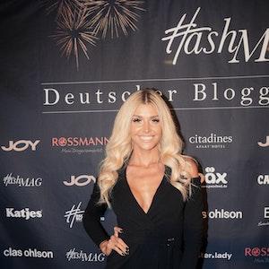 Gerda Lewis steht beim Deutschen Bloggerpreis vor einer Leinwand und lächelt für die Kameras.