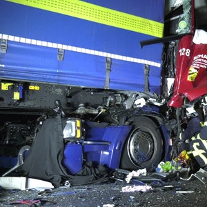 Einsatzkräfte der Feuerwehr untersuchen in der Nacht zum Mittwoch (13. Oktober 2021) die stark zerstörten Fahrerkabinen der verunfallten Lkw auf der A4.
