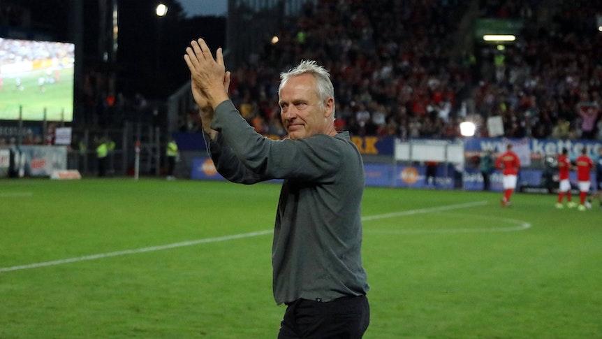 Trainer Christian Streich hat Tränen in den Augen und klatscht in Richtung der Fans auf der Südtribüne.