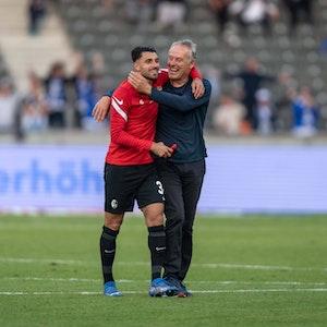 Christian Streich (r.) und Vincenzo Grifo (l.) laufen Arm und Arm über den Platz.