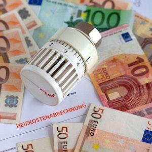Ein Heizungsthermostat liegt auf der Heizkostenabrechnung und Euro-Geldscheinen.