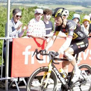 Tony Martin fährt auf seinem Rennrad, sein Arm und sein Bein sind verbunden.