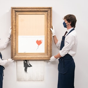 """Kunsthändler halten das zu versteigernde Bansky-Werk """"Love Is In The Bin"""" am 03.09.2021"""