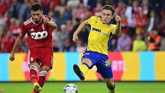 Borussia Mönchengladbach hat Rocco Reitz (r.) an den belgischen Erstligisten VV St. Truiden ausgeliehen. In dieser Szene ist der Mittelfeldspieler am 25. September 2021 in Lüttich im Duell mit Selim Amallah (l.) von Standard Lüttich zu sehen. Reitz streckt sein Bein aus und will einen Schuss blockieren.