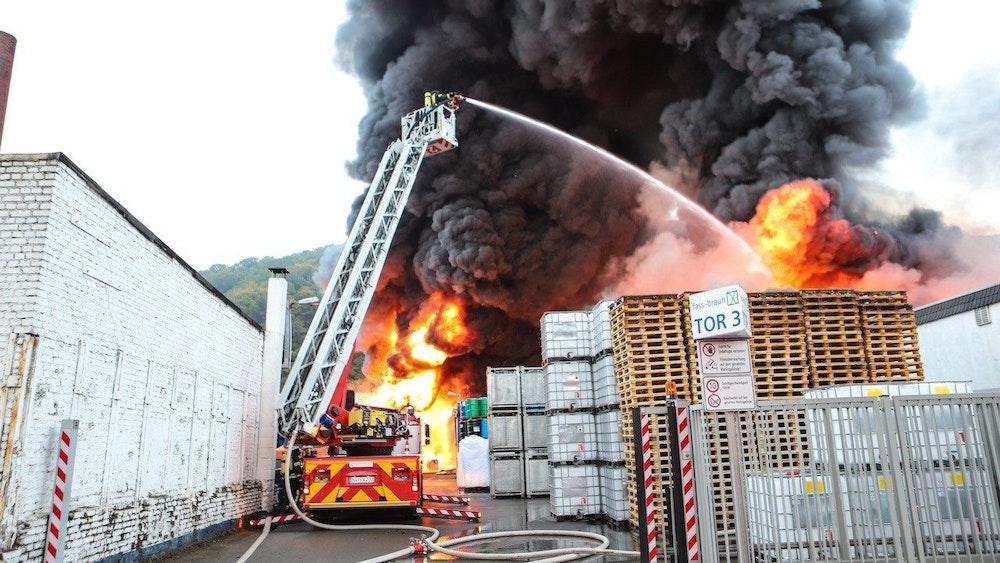 Flammen und dichter Rauch schlagen aus einem Firmengebäude.