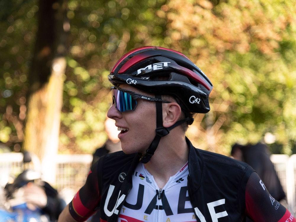 Tadej Pogacar lächelt nach einem langen Rennen. Auf seinem Kopf trägt er einen Helm. Außerdem trägt er eine Sonnenbrille.