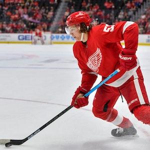 Moritz Seider läuft mit dem roten Trikot der Detroit Red Wings über das Eis und führt den Puck eng am Schläger.