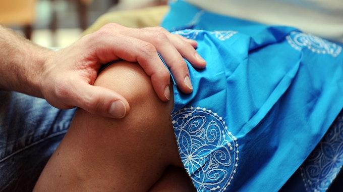 Die Hand eines Mannes liegt auf dem Knie einer Frau