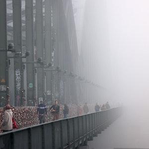 Spaziergänger gehen im Nebel über die Hohenzollernbrücke.