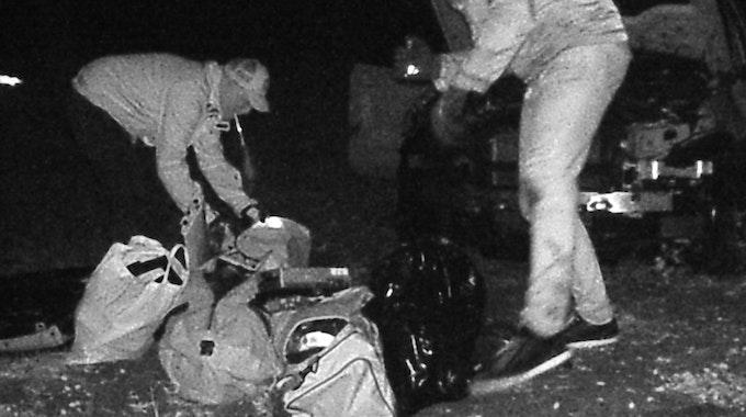 Auf dem Bild der Wildkamera sieht man, wie Unbekannte bei Nacht Einzelteile des ausgeschlachteten BMW in Taschen verstauen.