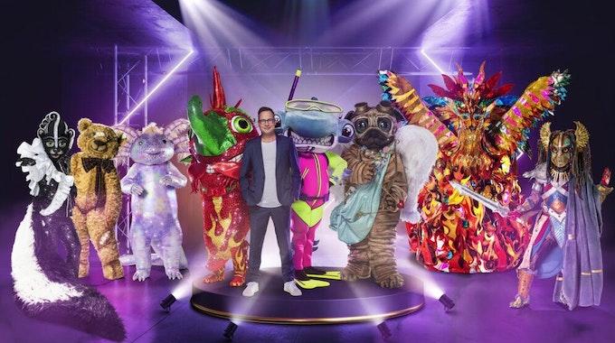 """Der Moderator der Show """"The Masked Singer"""" Matthias Opdenhövel steht mit acht Masken auf der Bühne."""
