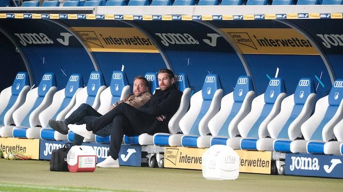Thomas Kessler und Jörg Jakobs sitzen bei der Partie TSG Hoffenheim gegen 1. FC Köln auf der Bank.