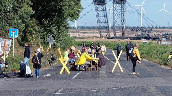 """Bei der Aktion """"Platz nehmen für Lützerath"""" sitzen Teilnehmer mit Stühlen und Tischen im Ort Lützerath auf der Straße am Tagebaurand."""