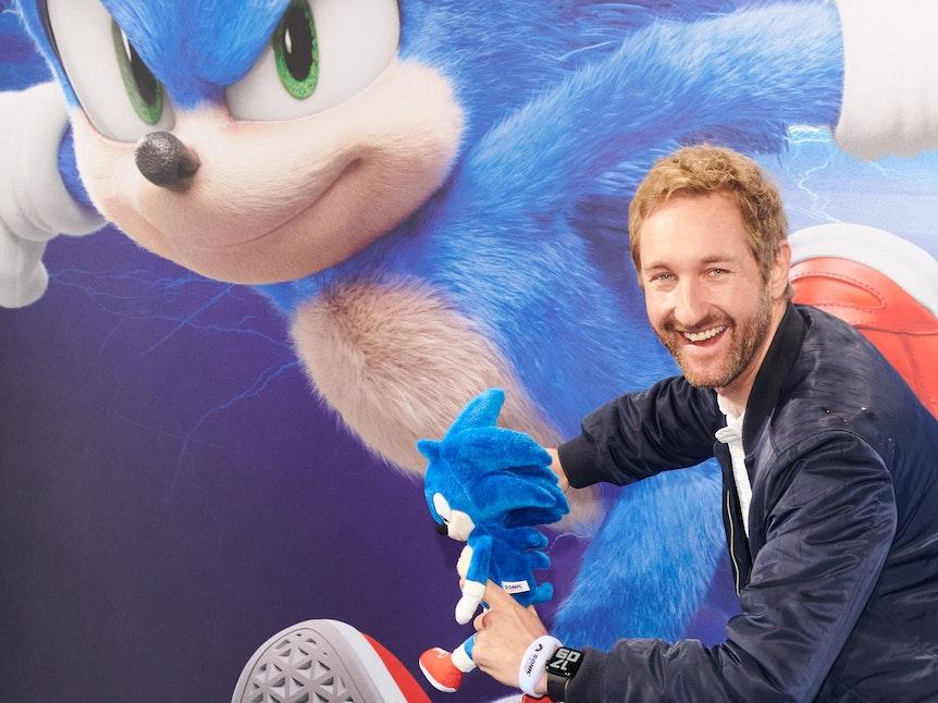 """Daniel Boschmann lächelt mit einer """"Sonic""""-Figur in der Hand in die Kamera."""