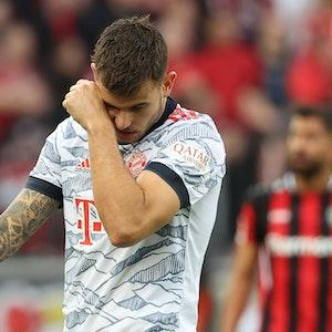 Bayern-Star Lucas Hernández wischt sich beim Spiel in Leverkusen durch das Gesicht.