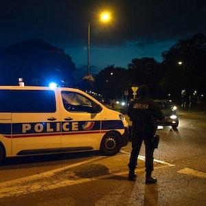 Ein Polizist steht neben einem Einsatzwagen an einem Tatort in der Nähe von Paris, aufgenommen im Oktober 2020.