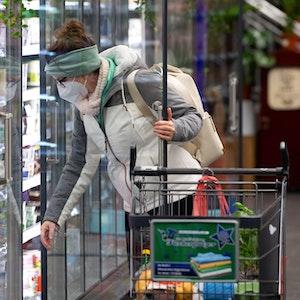 Eine Frau trägt bei ihrem Einkauf in einem Supermarkt eine FFP2-Schutzmaske.