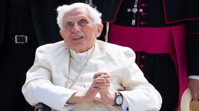 Der emeritierte Papst Benedikt XVI. bei einem Besuch in München 2020, er sitzt in einem Rollstuhl und hat die Hände gefaltet.