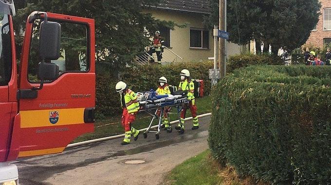 Rettungskräfte schieben eine Trage über die Straße.