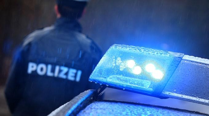 Ein Polizist steht am 15. März 2019 im Regen vor einem Streifenwagen, dessen Blaulicht aktiviert ist.