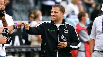 """Max Eberl, Sportdirektor von Borussia Mönchengladbach, hier am 13. August 2021, hält lächelnd das """"DAZN""""-Mikro in der Hand und gibt jemandem die Faust."""